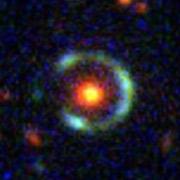 Красный объект – линзирующая галактика. Голубое кольцо – изображение линзируемой галактики; если бы не гравитационное линзирование, то её вряд ли удалось бы заметить. Кстати, благодаря этому явлению астрономы смогли узнать о ней кое-какие подробности. В частности то, что в ней происходит очень интенсивное звёздообразование (фото SDSS).